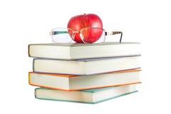 Libros con la manzana roja y vidrios en un fondo blanco Foto de archivo libre de regalías