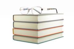 Libros con los vidrios en un fondo blanco Foto de archivo