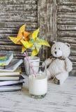Libros, cuadernos, diarios, molinillos de viento del papel hecho a mano y un vidrio de leche - lugar de trabajo del bebé Imagenes de archivo