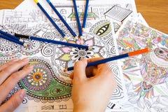 Libros de colorante adultos con los lápices, nueva tendencia del alivio de tensión, persona del concepto del mindfulness que colo Foto de archivo