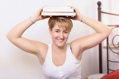 Libros de equilibrio de la mujer bastante joven en su cabeza Foto de archivo libre de regalías