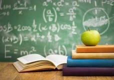Libros de escuela con la manzana en el escritorio imagen de archivo