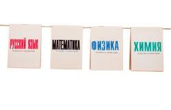 Libros de escuela vieja en una cuerda en blanco Fotografía de archivo