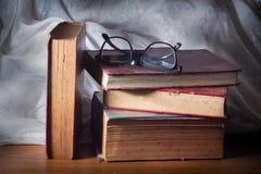 Libros de la pila con las lentes Fotos de archivo
