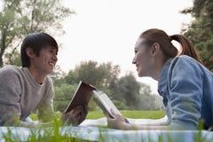 Libros de lectura adolescentes de los pares en el parque Foto de archivo libre de regalías