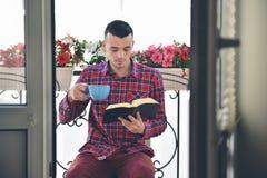 Libros de lectura barbudos concentrados del hombre y café o té de consumición Foto de archivo libre de regalías