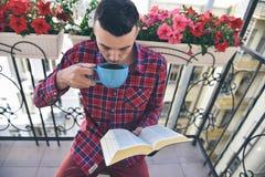 Libros de lectura barbudos concentrados del hombre y café o té de consumición Imagen de archivo libre de regalías