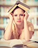 Libros de lectura cansados de la muchacha del estudiante Imágenes de archivo libres de regalías