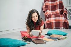 Libros de lectura de la muchacha en un piso imagenes de archivo