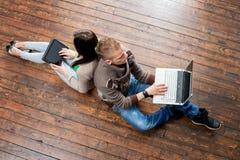 Libros de lectura de la muchacha y del muchacho que se inclinan en uno a en piso de madera Imagen de archivo libre de regalías