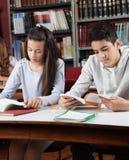 Libros de lectura de los alumnos en biblioteca Foto de archivo libre de regalías