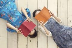 Libros de lectura de los amigos mientras que miente en piso Imagen de archivo