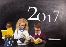 Libros de lectura de los niños contra la pizarra con la muestra del Año Nuevo 2017 Foto de archivo libre de regalías