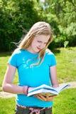 Libros de lectura del adolescente de la chica joven al aire libre Imagenes de archivo