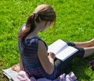 Libros de lectura del estudiante en el parque Imágenes de archivo libres de regalías