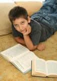 Libros de lectura del muchacho en el suelo Fotos de archivo libres de regalías