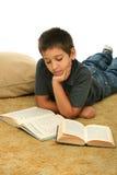 Libros de lectura del muchacho en el suelo Imagen de archivo libre de regalías