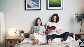 Libros de lectura hermosos de los pares que se sientan en la cama en casa junto que disfruta de la afición metrajes