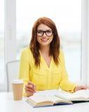 Libros de lectura sonrientes de la muchacha del estudiante en biblioteca Fotografía de archivo libre de regalías