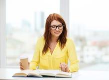 Libros de lectura sonrientes de la muchacha del estudiante en biblioteca Imagen de archivo libre de regalías