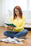 Libros de lectura sonrientes de la muchacha del estudiante en casa Fotografía de archivo