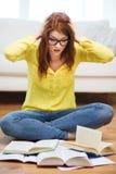Libros de lectura sonrientes de la muchacha del estudiante en casa Foto de archivo libre de regalías