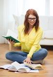 Libros de lectura sonrientes de la muchacha del estudiante en casa Imágenes de archivo libres de regalías