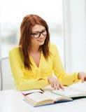 Libros de lectura sonrientes de la muchacha del estudiante en universidad Imagen de archivo libre de regalías