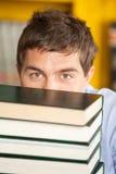Libros de Peeking Over Piled del estudiante en universidad Fotos de archivo libres de regalías
