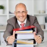 Libros de With Stack Of del hombre de negocios que gesticulan los pulgares para arriba Imagen de archivo libre de regalías