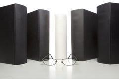Libros de tapa dura con los vidrios de una lectura en frente Imagenes de archivo