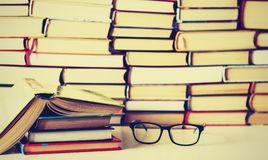 Libros del libro encuadernado en la tabla de madera blanca, el libro abierto y los vidrios, espacio de la copia para el texto fotografía de archivo