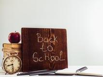 Libros del vintage, reloj viejo, lápices, manzana roja y pizarra Foto de archivo