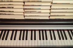 Libros en el piano Concepto de literatura y de música imagenes de archivo