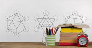 Libros en la tabla contra la pizarra blanca con los gráficos de la educación y de nuevo al texto de escuela Imagen de archivo libre de regalías