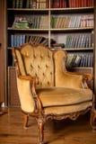 Libros en los estantes Butaca amarilla de lujo en sitio de la biblioteca Todavía vida de la silla del vintage Muebles viejos del  imágenes de archivo libres de regalías