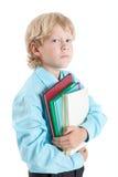 Libros jovenes del abarcamiento del alumno del muchacho con las manos, mirando la cámara, aislada en el fondo blanco Fotos de archivo libres de regalías