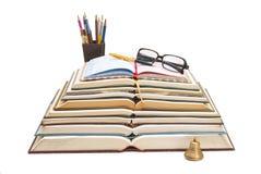 Libros, plumas y gafas de sol en una sola composición Imagen de archivo libre de regalías