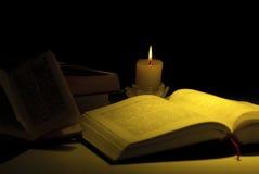 Libros por la luz de la vela Fotografía de archivo