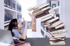 Libros que caen de los controles femeninos del estudiante universitario Fotografía de archivo libre de regalías