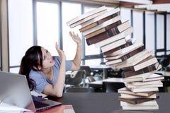 Libros que caen de los controles hermosos del estudiante universitario Fotos de archivo libres de regalías