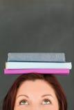 Libros que desgastan felices de la mujer joven en su cabeza Fotos de archivo libres de regalías