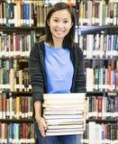 Libros que llevan del estudiante en la biblioteca Fotos de archivo libres de regalías