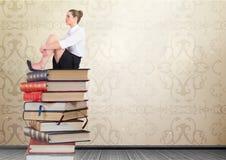 Libros que se sientan de la empresaria apilados por la antigüedad decorativa del papel pintado Foto de archivo