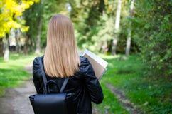 Libros que se sostienen al aire libre de la muchacha adolescente Imagenes de archivo