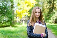 Libros que se sostienen al aire libre de la muchacha adolescente Fotos de archivo