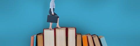 Libros que suben de la mujer de negocios con el fondo azul Foto de archivo libre de regalías