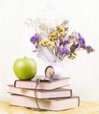 Libros, reloj antiguo y flores imagenes de archivo