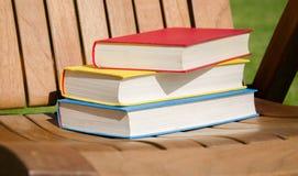 Libros rojos, amarillos y azules en una silla de madera Imagen de archivo