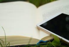 Libros, smartphone en un fondo de la hierba verde, concepto de educación y formación Imagen de archivo